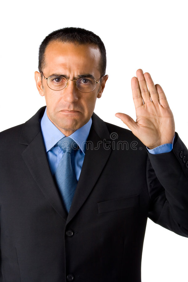 Businessman making vow. Middle aged businessman with raised hand making vow or pledge, white studio background royalty free stock images