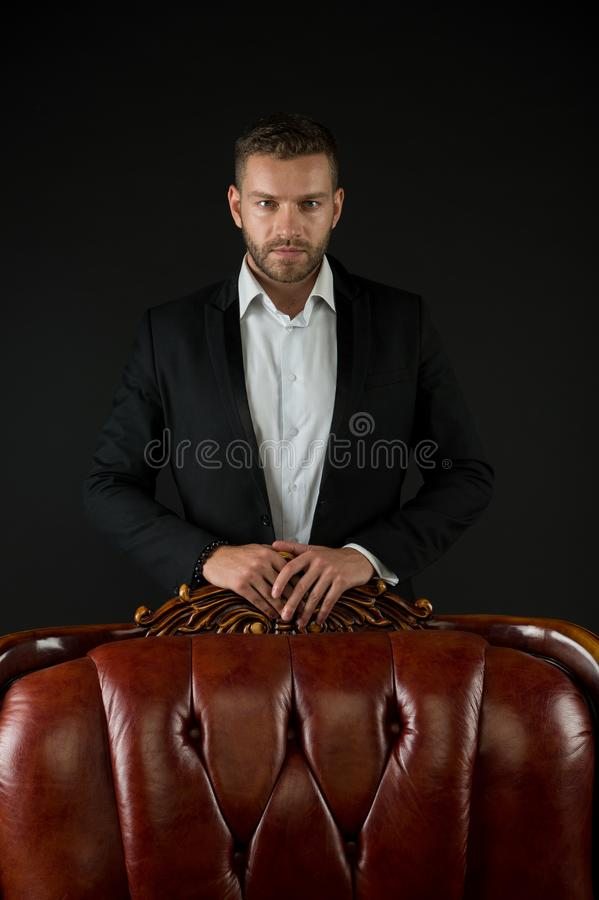 Businessman or man in formal suit on dark background. Man on serious face posing behind leather armchair. Business. Success concept. Man with bristle looks royalty free stock photography