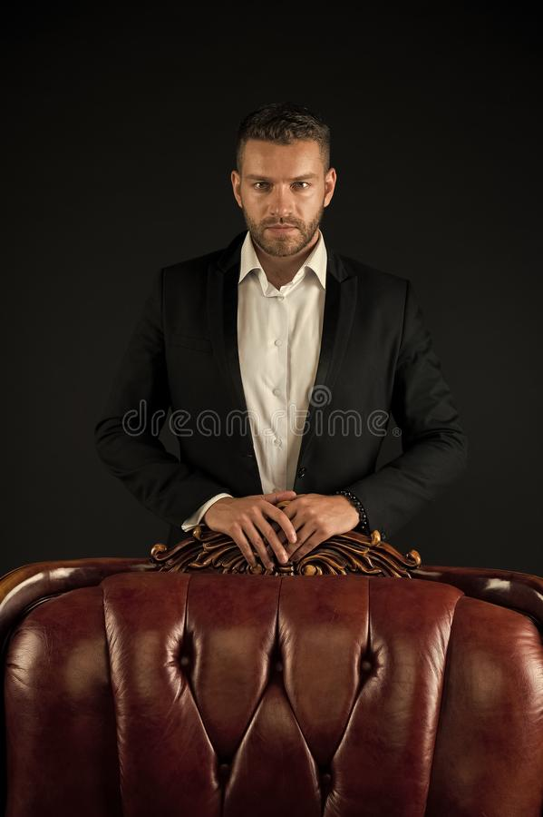 Businessman or man in formal suit on dark background. Man on serious face posing behind leather armchair. Business. Success concept. Man with bristle looks royalty free stock photo