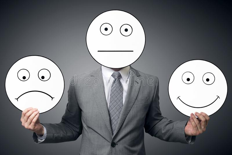 Businessman with mask of different emotions. Businessman holding smile and sad mask. Conceptual image of a man changing his mood f. Rom bad to good stock images