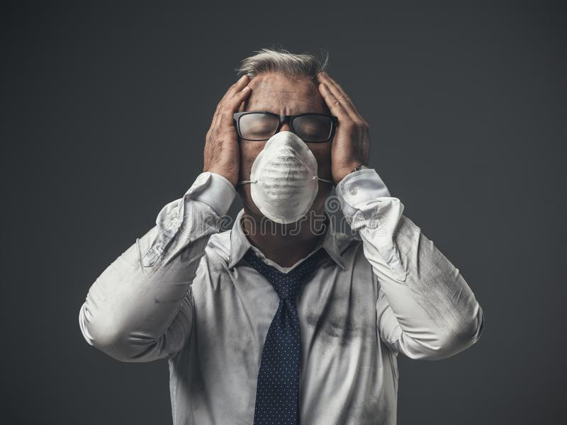 Businessman with mask and head in hands. Desperate corporate businessman with protective mask and head in hands, air pollution concept stock images