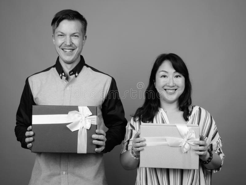 Businessman and mature Asian businesswoman holding gift box stock images