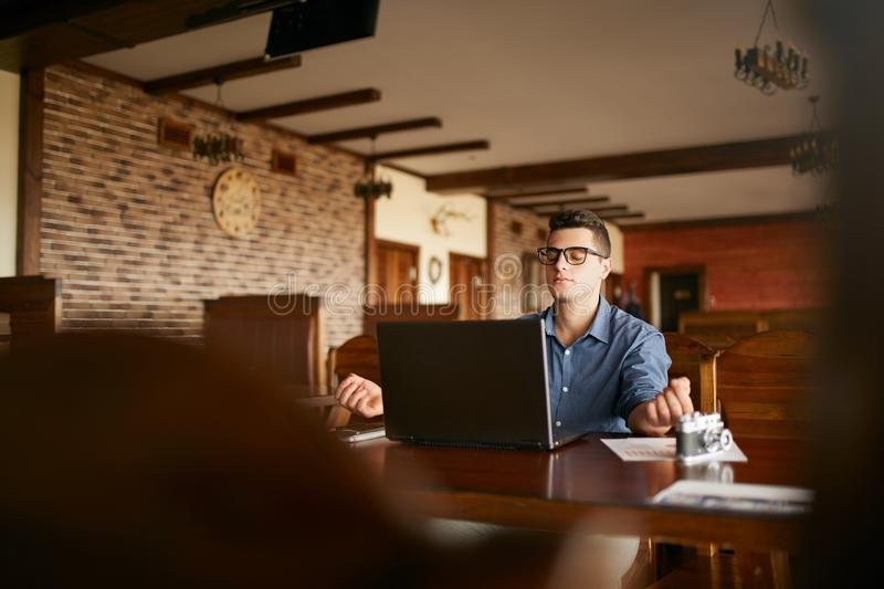 Businessman meditates sitting at table and laptop in office. Company leader practicing yoga during break at work for stock images