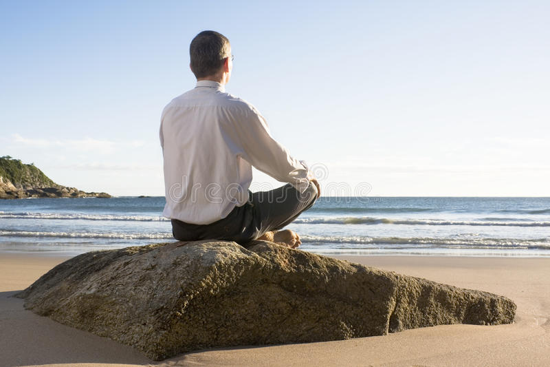 Businessman meditating on a beach. Businessman meditating on a sunny beach in the morning stock photo