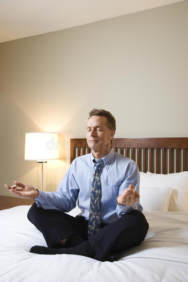 Businessman Meditating on Bed. Caucasian businessman sits on a bed in the lotus position while meditating with closed eyes. Vertical shot royalty free stock photo