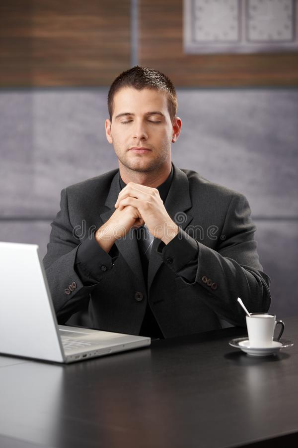 Businessman meditating at desk. In office royalty free stock images