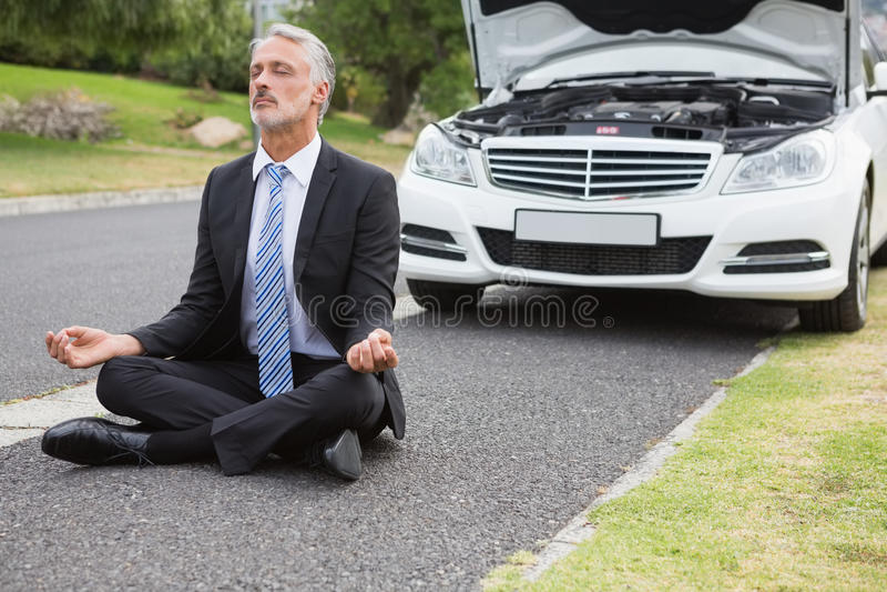 Businessman meditating after his car broken down royalty free stock photo