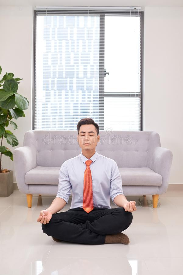 Businessman meditating in lotus pose on the floor in the office stock image