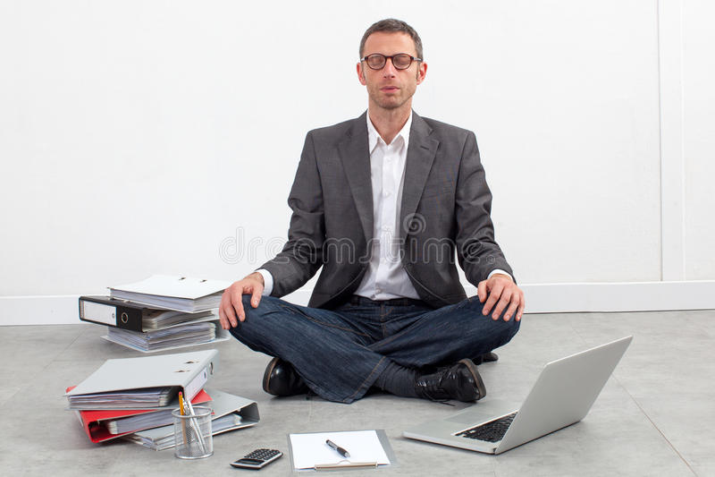 Businessman meditating at office having break at work stock photos