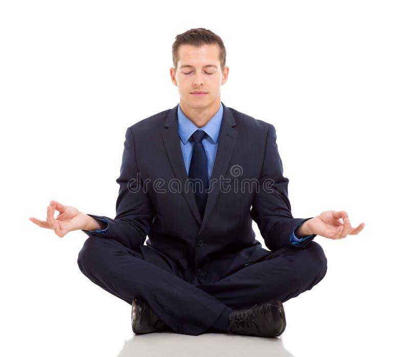 Businessman meditating. Peaceful businessman meditating on white background stock photography