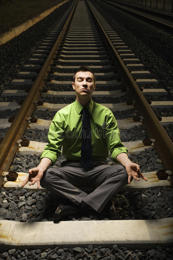 Download Businessman Meditating On Railroad Tracks. Stock Photo - Image: 12732230