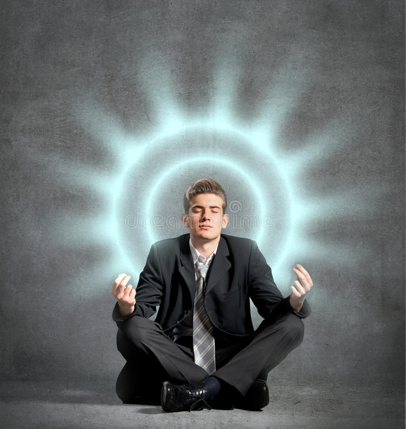 Businessman meditating. Relaxing, in front of a wall royalty free stock photography