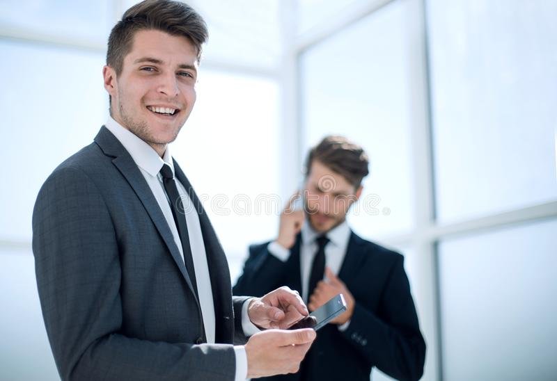 Image of young businessman using smartphone on background of his stock images