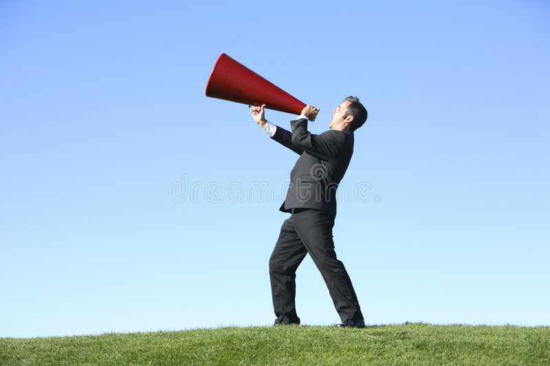 Businessman with megaphone. Businessman outside yelling through a red megaphone royalty free stock photos