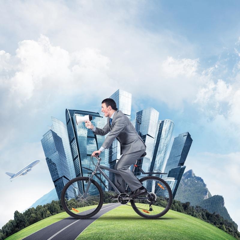 Businessman with megaphone in hand on bike. Corporate employee announcing in loudspeaker. Man in business suit riding bicycle on road and world round panorama stock photography
