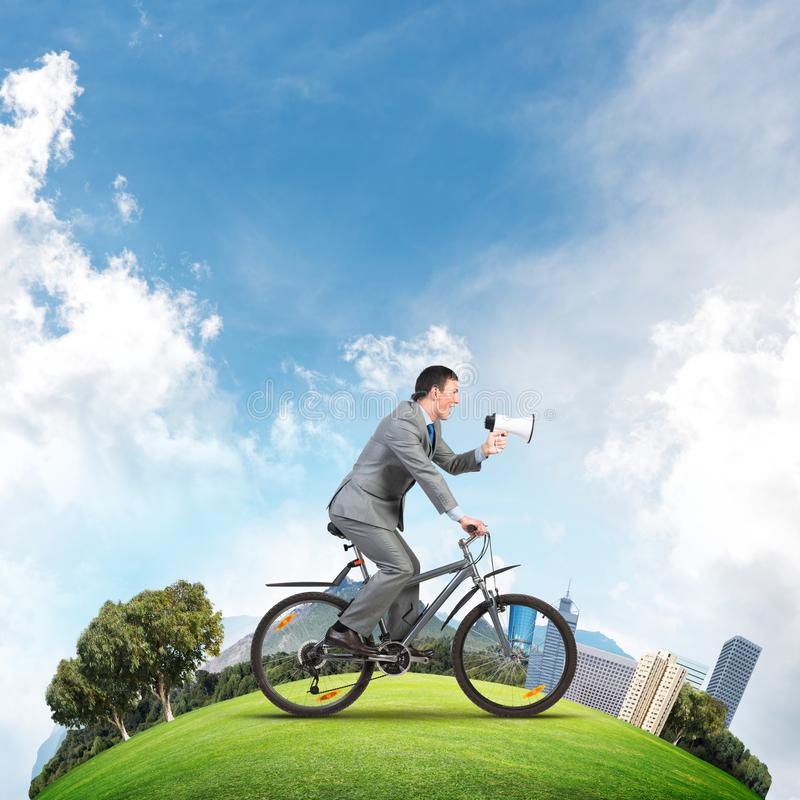 Businessman with megaphone in hand on bike. Corporate employee announcing in loudspeaker. Man in business suit riding bicycle on green field. Handsome cyclist royalty free stock image