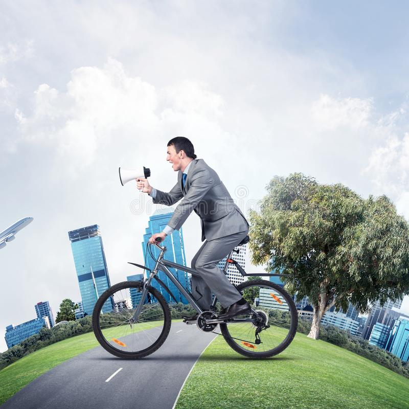 Businessman with megaphone in hand on bike. Corporate employee announcing in loudspeaker. Man in business suit riding bicycle on road and world round panorama royalty free stock image