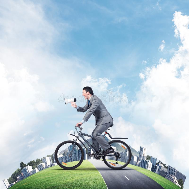 Businessman with megaphone in hand on bike. Corporate employee announcing in loudspeaker. Man in business suit riding bicycle on road. Handsome cyclist and stock images