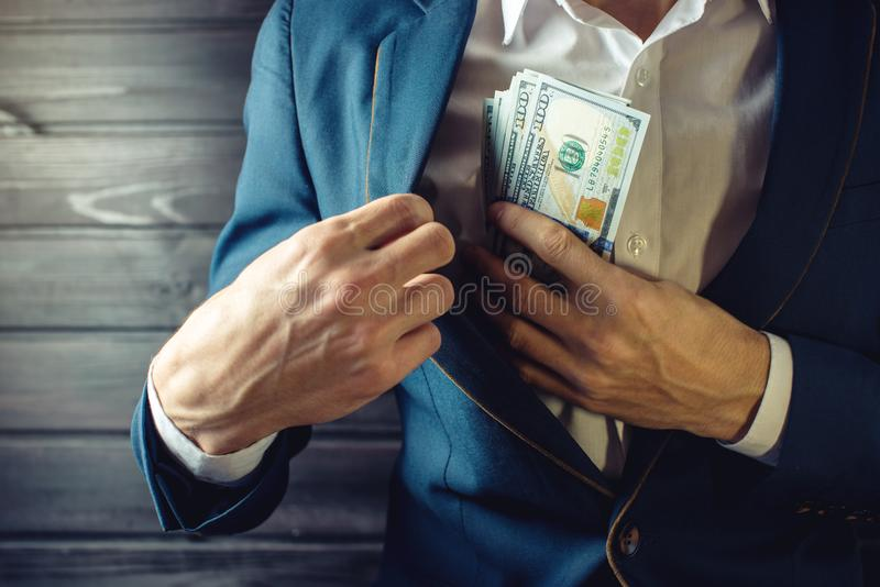 Businessman, member or officer puts a bribe in his pocket. Man businessman, member or officer in a suit puts a bribe in the form of hundred dollar bills in his stock photos