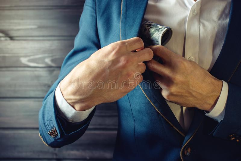 Businessman, member or officer puts a bribe in his pocket. Man businessman, member or officer in a suit puts a bribe in the form of hundred dollar bills in his stock images