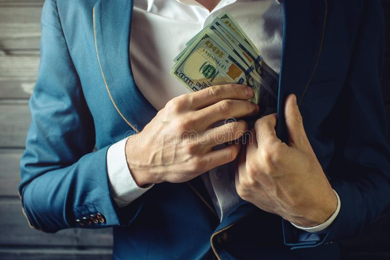 Businessman, member or officer puts a bribe in his pocket. Man businessman, member or officer in a suit puts a bribe in the form of hundred dollar bills in his royalty free stock images