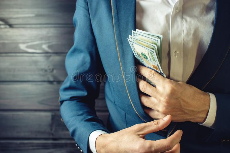 Businessman, member or officer puts a bribe in his pocket. Man businessman, member or officer in a suit puts a bribe in the form of hundred dollar bills in his royalty free stock photos
