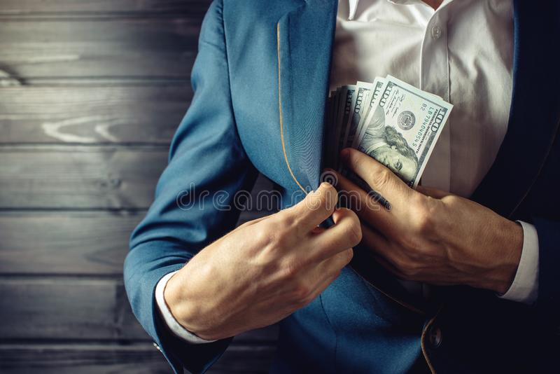 Businessman, member or officer puts a bribe in his pocket. Man businessman, member or officer in a suit puts a bribe in the form of hundred dollar bills in his stock photo