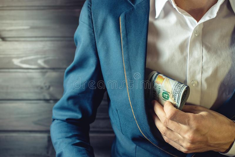 Businessman, member or officer puts a bribe in his pocket. Man businessman, member or officer in a suit puts a bribe in the form of hundred dollar bills in his stock photography