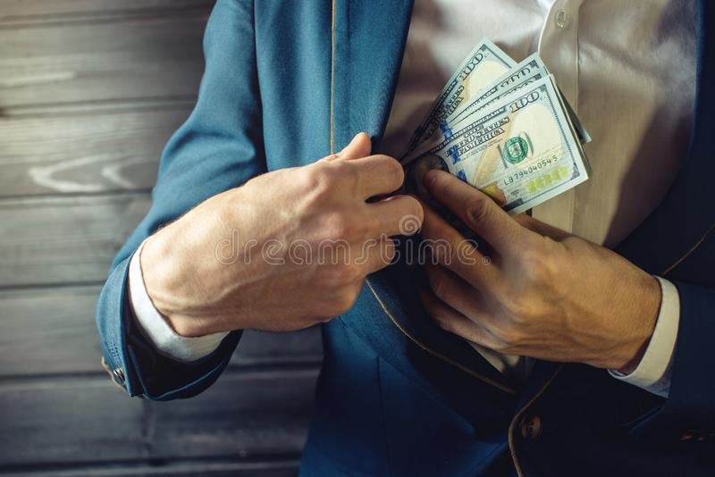 Businessman, member or officer puts a bribe in his pocket. Man businessman, member or officer in a suit puts a bribe in the form of hundred dollar bills in his stock image