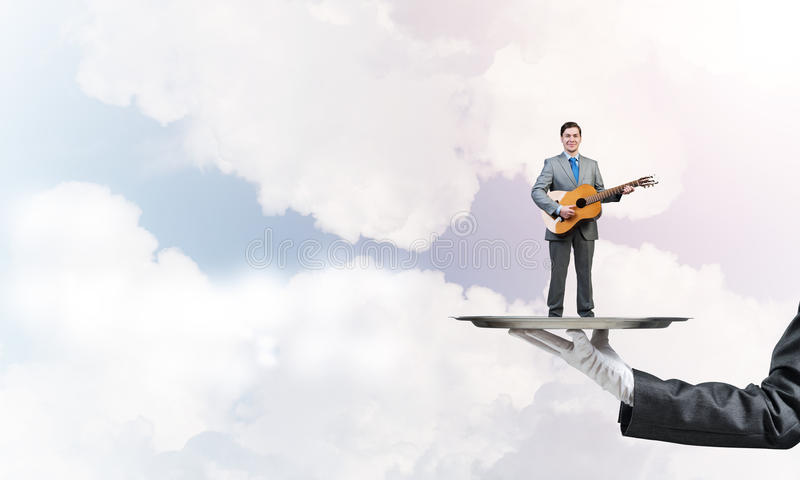 Businessman on metal tray playing acoustic guitar against blue sky background. Hand of waiter presenting on tray man playing guitar stock images
