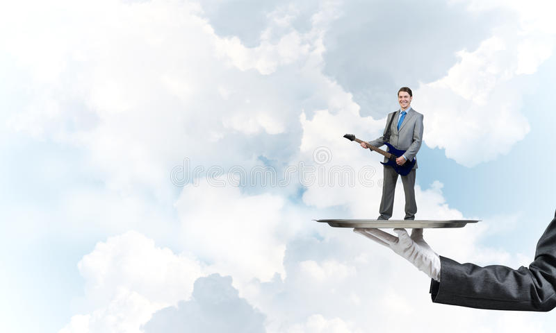 Businessman on metal tray playing electric guitar against blue sky background. Hand of waiter presenting on tray man playing guitar stock photo