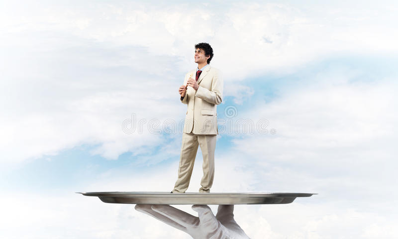 Businessman on metal tray playing fife against blue sky background. Hand of waiter presenting on tray man playing fife stock image