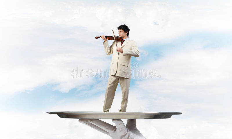 Businessman on metal tray playing violin against blue sky background. Hand of waiter presenting on tray man playing violin stock images