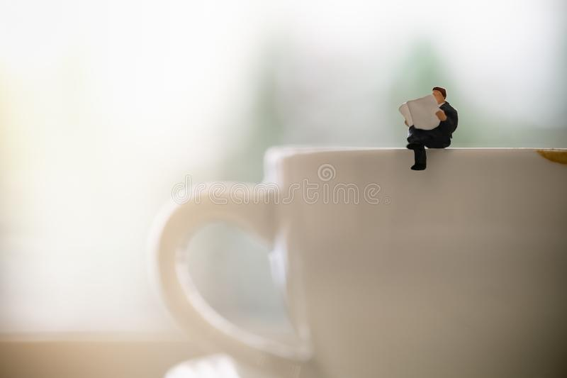 Businessman miniature figure sitting and reading a newspaper on dirty cup of hot coffee with copy scape stock image