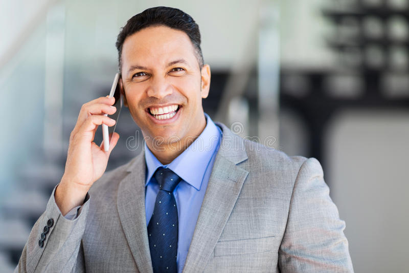 Businessman mobile phone. Cheerful middle aged businessman talking on mobile phone royalty free stock image