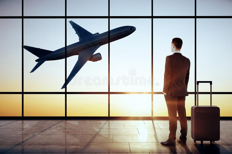Businessman in modern airport interior. Businessman standing in modern airport interior with flying by airplane and sunlight view in panoramic window stock photos