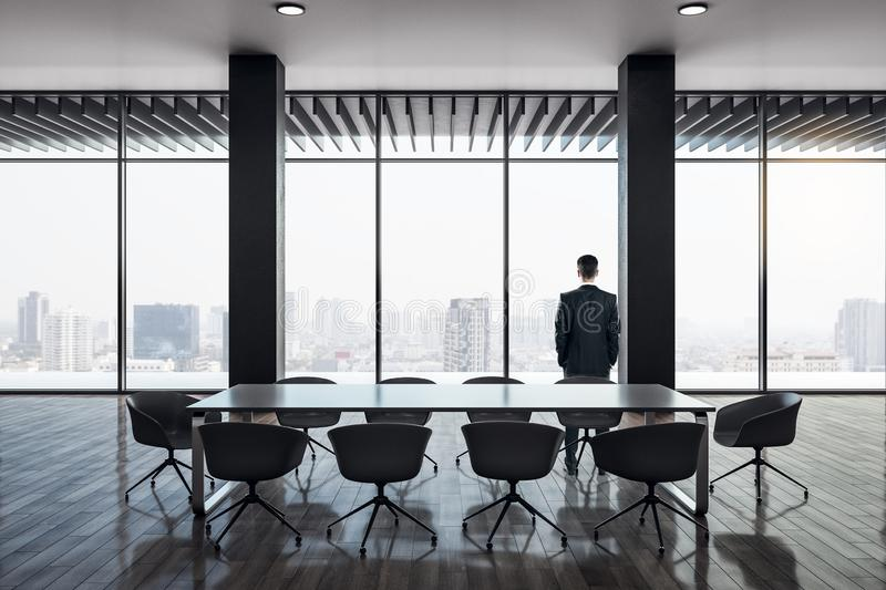 Businessman in modern conference room. Back view of businessman standing in modern conference room interior with panoramic city view, reflections on wooden floor stock photography