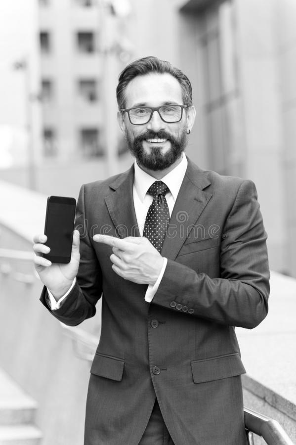 Businessman and modern gadget. Smiling businessman pointing finger at blank screen mobile phone isolated over building background. Happy businessman pointing stock images