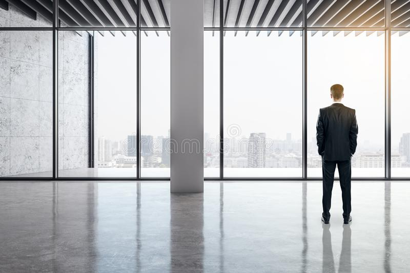 Businessman in modern office. Back view of businessman standing in modern office interior with panoramic city view, reflections on concrete floor and daylight royalty free stock photos