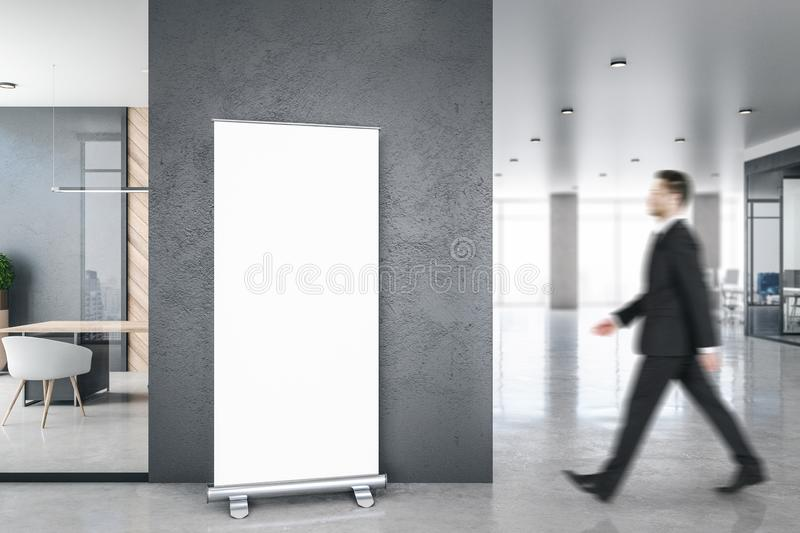 Businessman in modern office with banner. Side view of businessman walking in modern blurry office room interior with city view, empty banner and daylight. Mock stock image