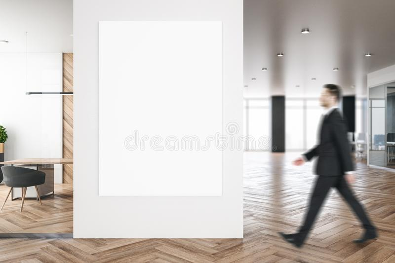 Businessman in modern office with billboard. Side view of businessman walking in modern blurry office room interior with city view, empty billboard and daylight stock image
