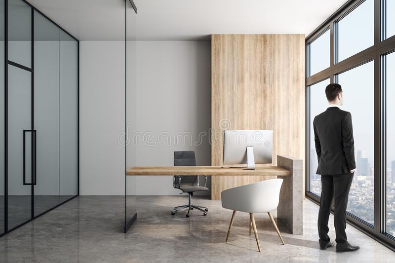 Businessman in modern office with concrete floor and wooden table stock photo