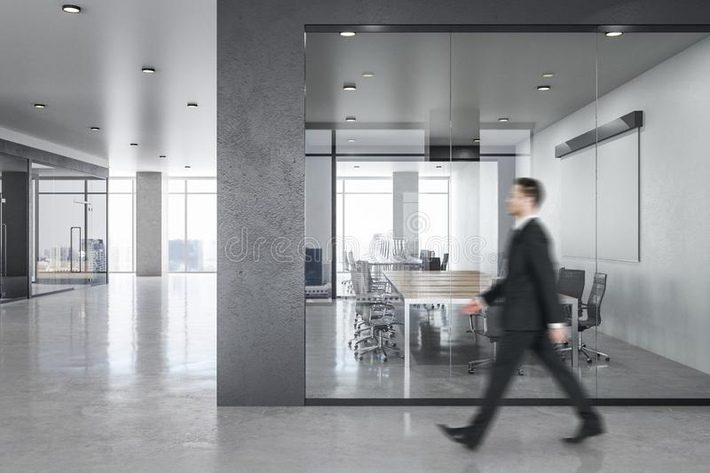 Businessman in modern office. Side view of blurry businessman walking in modern spacious office room interior with city view and daylight. Executive concept stock photo