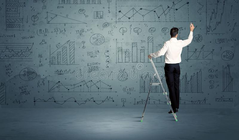 Man on ladder drawing charts. A businessman in modern stylish elegant suit standing on a small ladder and drawing pie and block charts on grey wall background royalty free stock photos