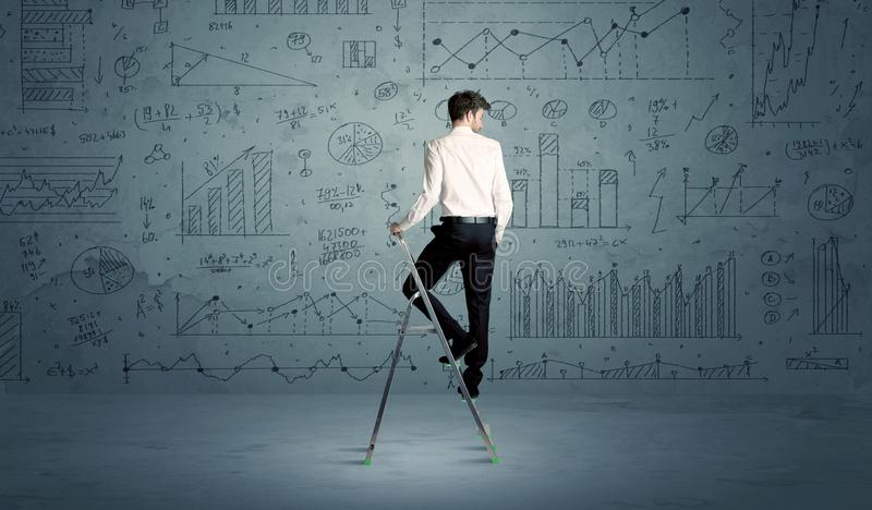 Man on ladder drawing charts. A businessman in modern stylish elegant suit standing on a small ladder and drawing pie and block charts on grey wall background stock image
