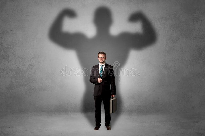 Businessman with muscular shade behind his back royalty free stock images