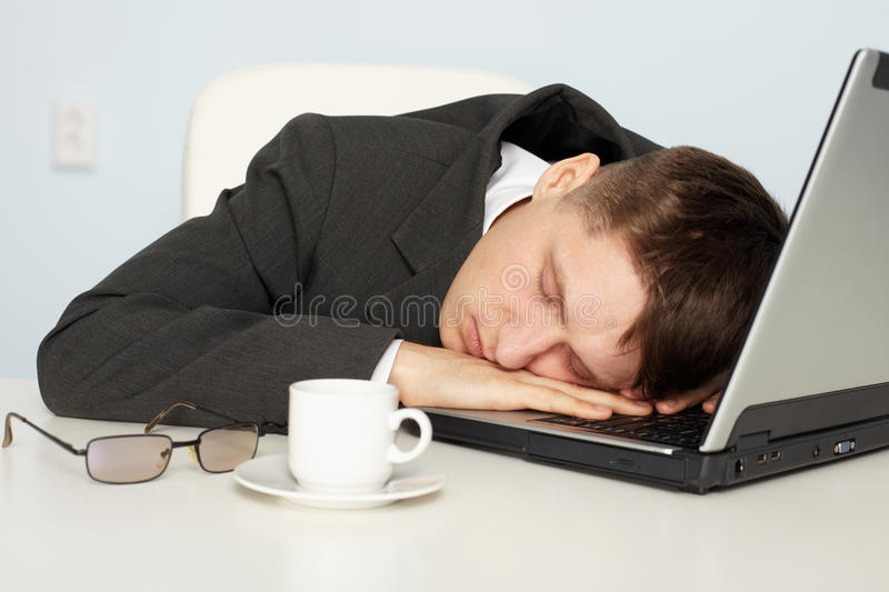 Businessman not enough sleep. A young businessman not enough sleep and fell asleep on the job royalty free stock image