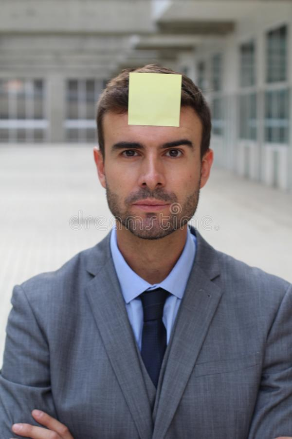 Businessman with a note on his forehead stock images