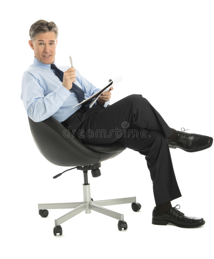 Businessman With Note Pad And Pen Sitting On Office Chair Royalty Free Stock Photo