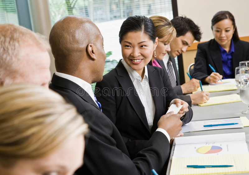 Businessman offering business card to colleague stock photo